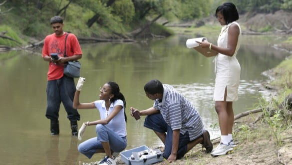 Students standing by river analyzing water