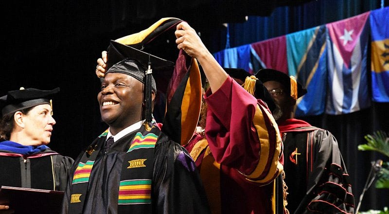 Male student at Bethune Cookman University receiving conferral during graduation ceremony wearing cap and gown