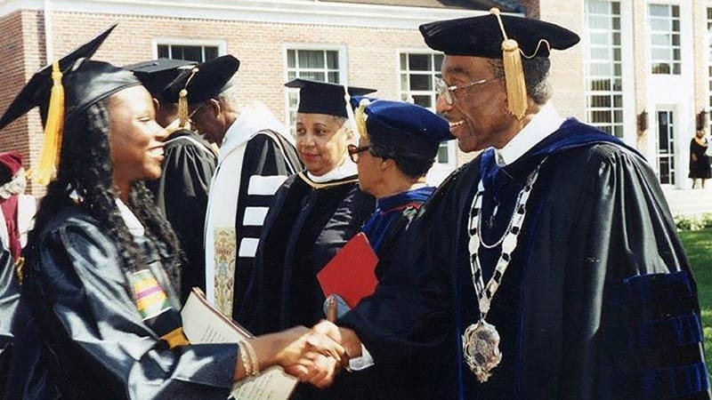 Oswald Bronson shakes hands during a graduation ceremony