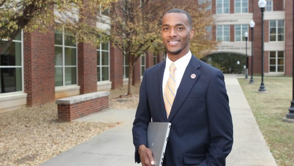 Male college student with laptop wearing a suit outside on college campus