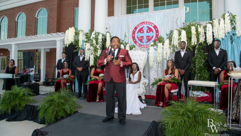 Dr. Hawkins speaking onstage at coronation with Miss Talladega and others sitting behind him