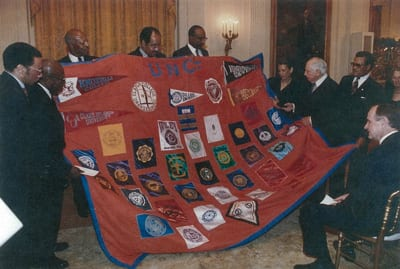 Ambassador Annenberg at the White House receives quilt from UNCF Pres. William H. Gray and UNCF presidents William McMillan, Sr. (Rust), Prezell Robinson (St. Augustine's), Oswald Bronson (Bethune-Cookman), Johnetta Cole (Spelman) and Talbert Shaw (Shaw).