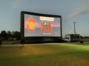 Outdoor movie screen with logos Dreamgirls poster projected