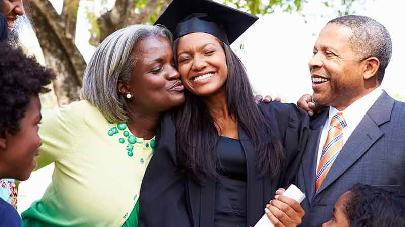family celebrating with female college graduate in cap and gown with diploma