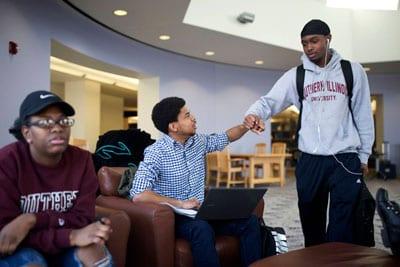 "Rozzie Caribs (center) greets his friend Calvin Stewart during a ""study jam"" at the library at Southern Illinois University, Carbondale on April 10. Cribbs received a full-ride college scholarship through the Jordan Brand's Wings program."