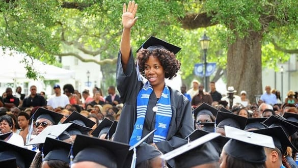 A girl is lifted above the crowd during a graduation celebration