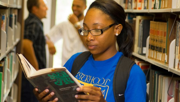 Voorhees College student reading a book in library stacks