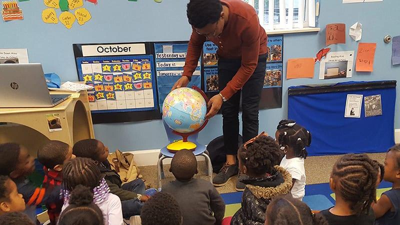 Black male teacher with children