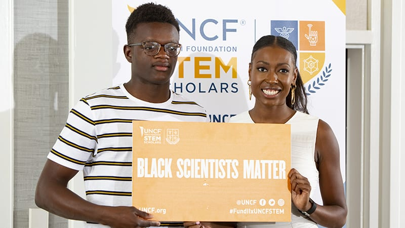 two people holding black scientists matter sign