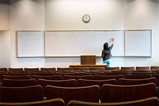 Empty classroom with a woman writing on a white board