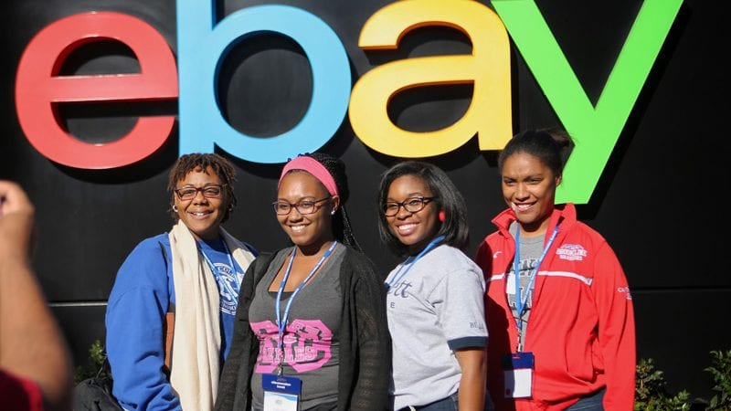 4 female college students standing under an eBay sign