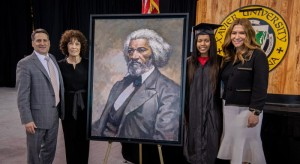 Group standing with portrait of Frederick Douglass