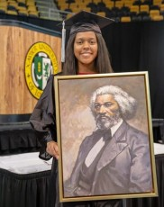 Xavier Univ. senior Sydney Green holding portrait of Frederick Douglass