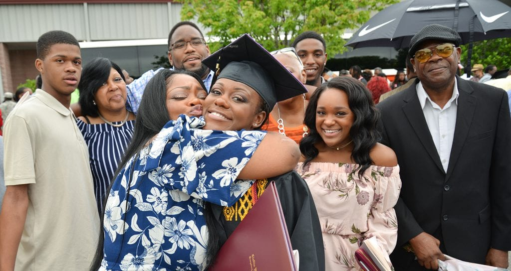Parents celebrating with their daughter who's wearing a cap and gown after graduation