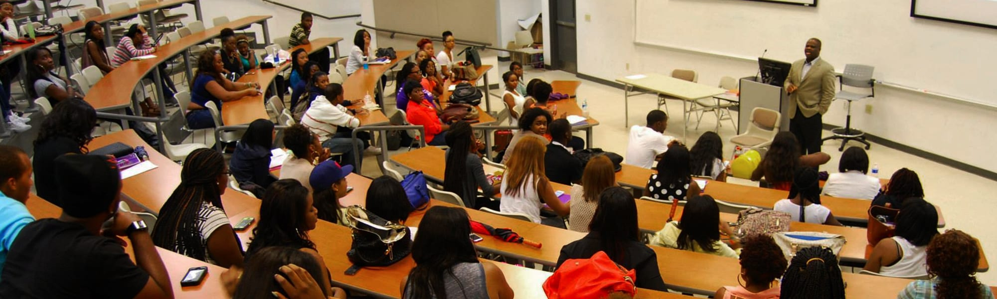 Group shot of students sitting in class listening to a professor give a lecture