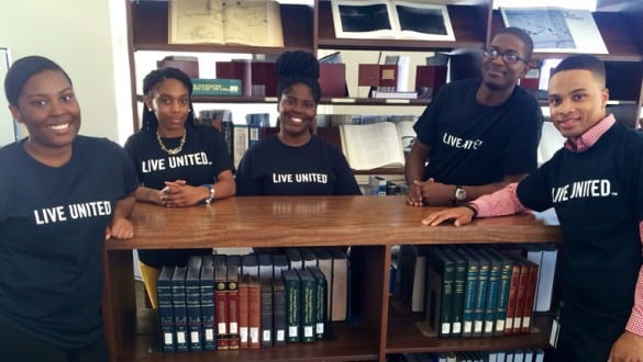 Group shot of 5 Allen University students in library wearing Live United t-shirts