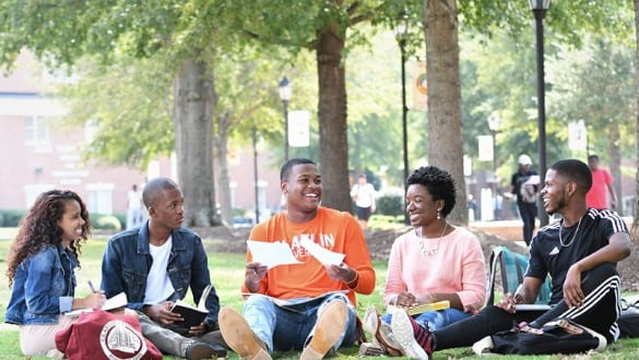 5 Claflin University students sitting on grassy campus outdoors