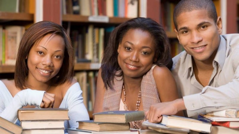 Group shot of 3 Claflin University students in library with books
