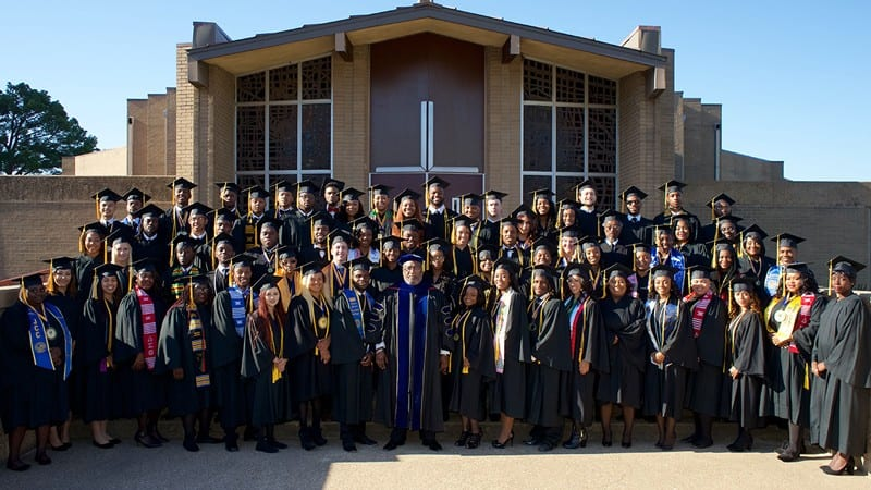Group shot of graduates from Jarvis Christian College wearing caps and gowns