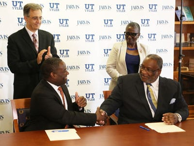 Jarvis Christian College President Dr. Lester C. Newman (right) and UT Tyler President Dr. Michael Tidwell shake hands after signing a memorandum of understanding.