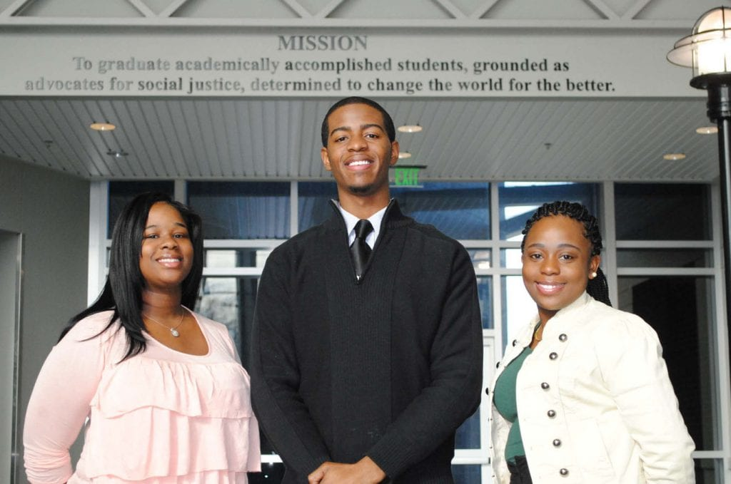 Group shot of 3 Philander Smith College students smiling in front of building