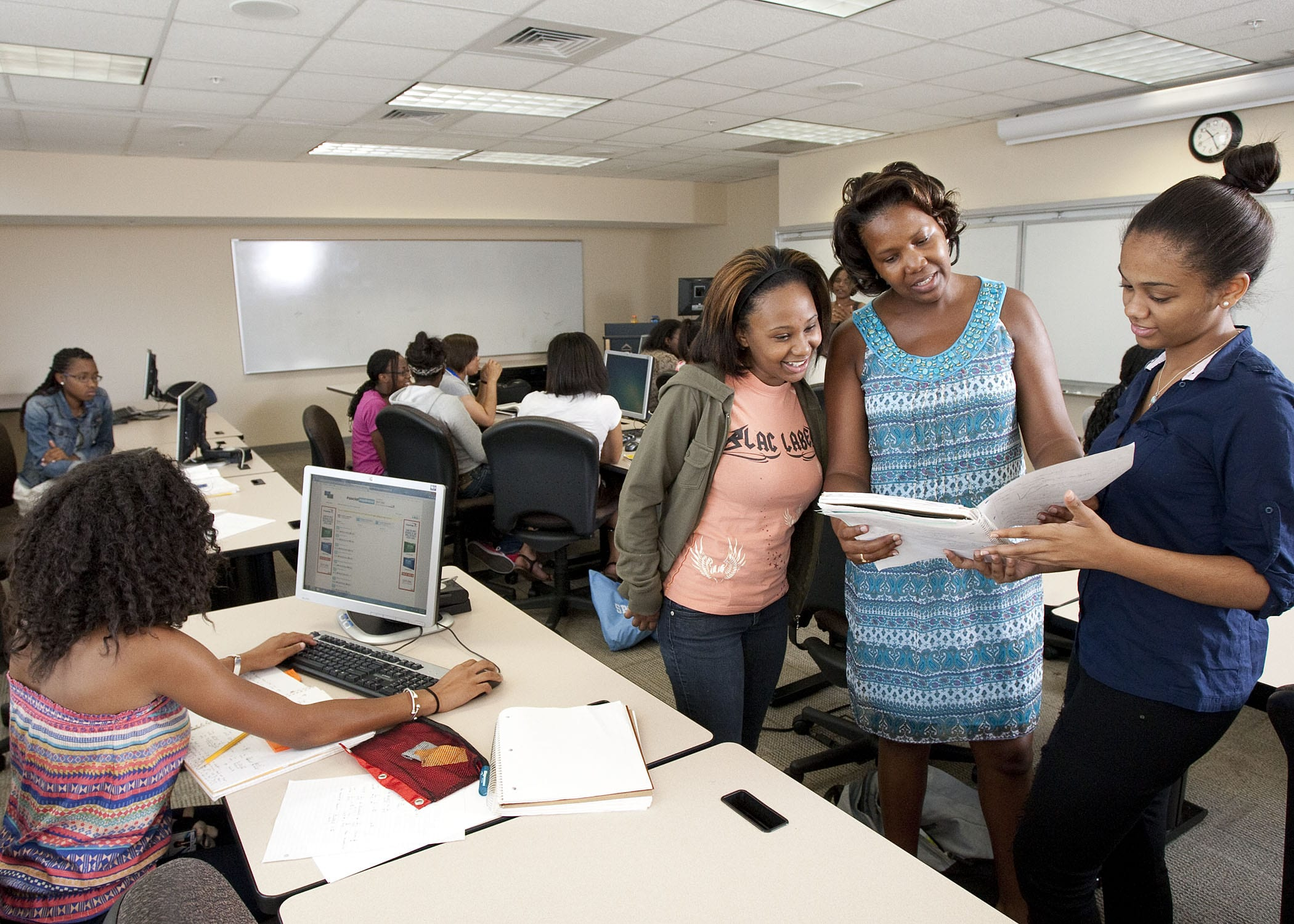 Image of a professor and several students working together in classroom near computers
