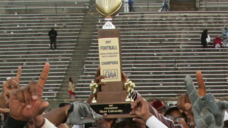 Shaw University football players holding a trophy following football game