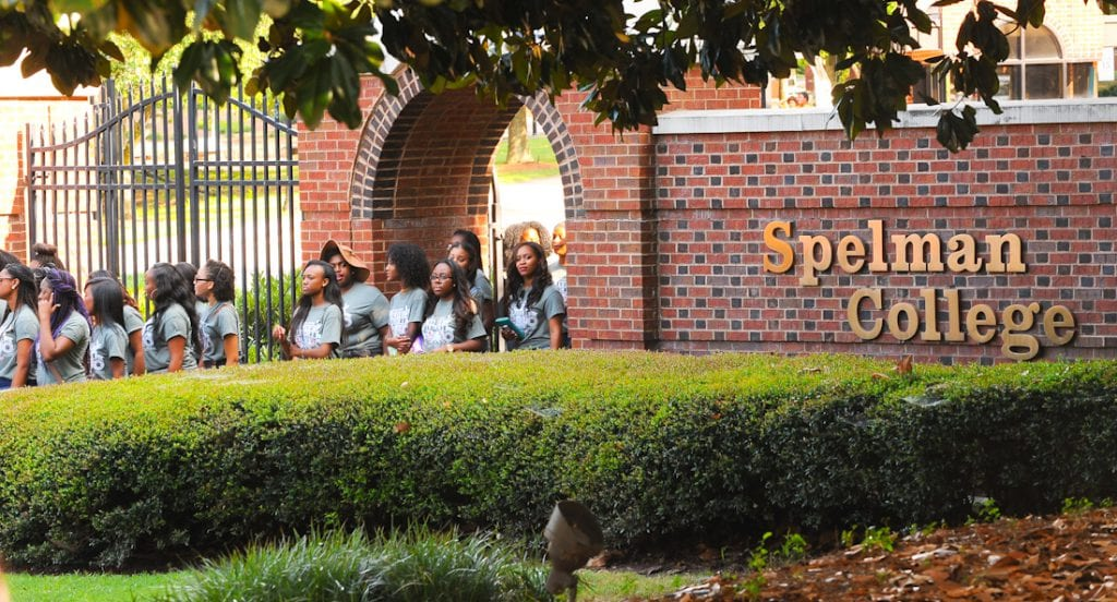 Group shot of Spelman College students walking outside past college sign