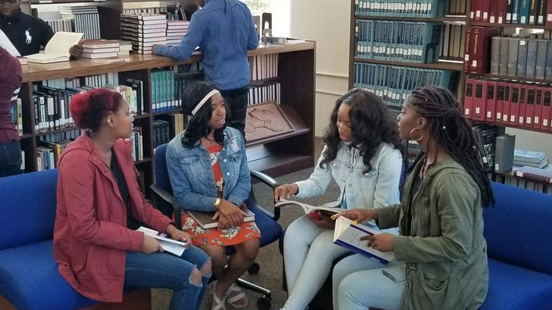 Four students at Allen University talking in library