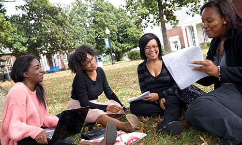 Group shot of 4 female students talking and sitting outside on Bennett College campus