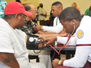 Man at Cookman taking a patient's blood pressure