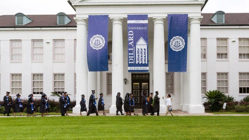 Dillard University building with graduates wearing caps and gowns walking in front
