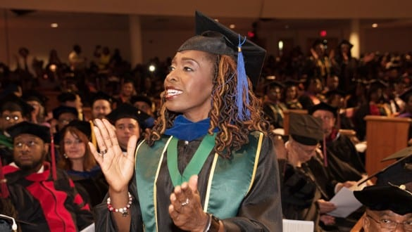 Female professor at Edward Waters College graduation ceremony wearing her cap and gown