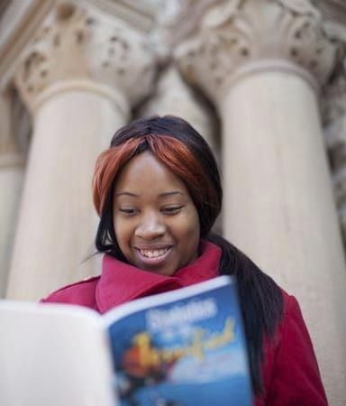 Female Fisk University student reading a book outside