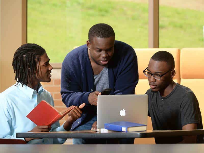 3 male Oakwood University students studying with a laptop