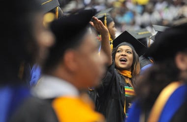 Female student wearing cap and gown cheering during graduation ceremony at Oakwood University
