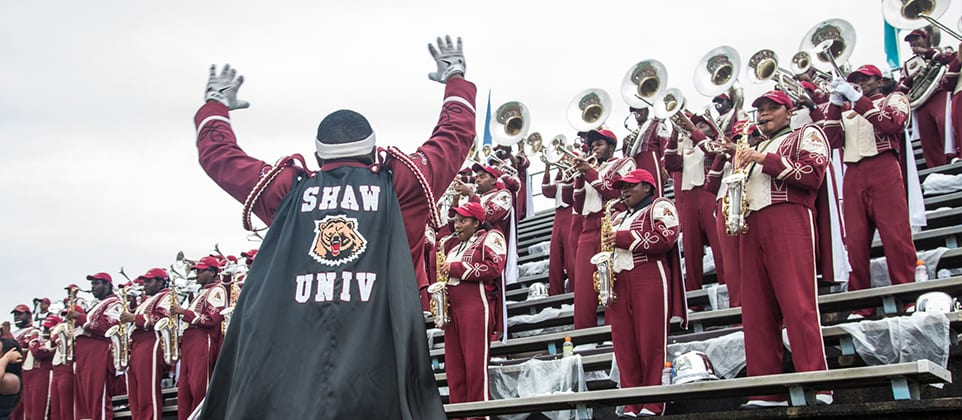 Group shot of Shaw University marching band members performing in stands during game