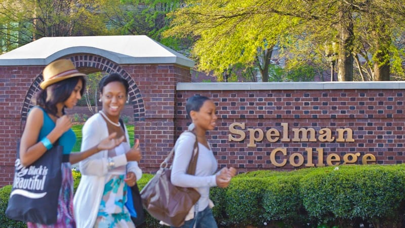 Sign at Spelman College with students walking nearby