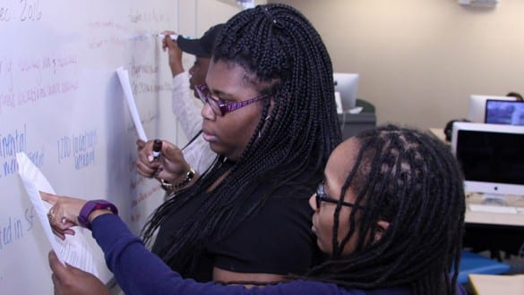 3 Spelman College students working at a white board