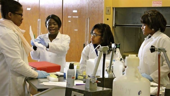 Group shot of 4 female Tougaloo College students working together in laboratory