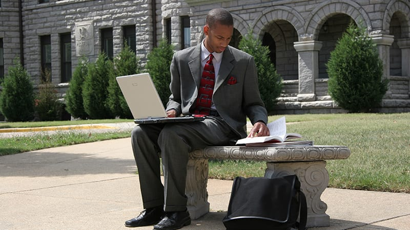 Male student with laptop working at Virginia Union University outside