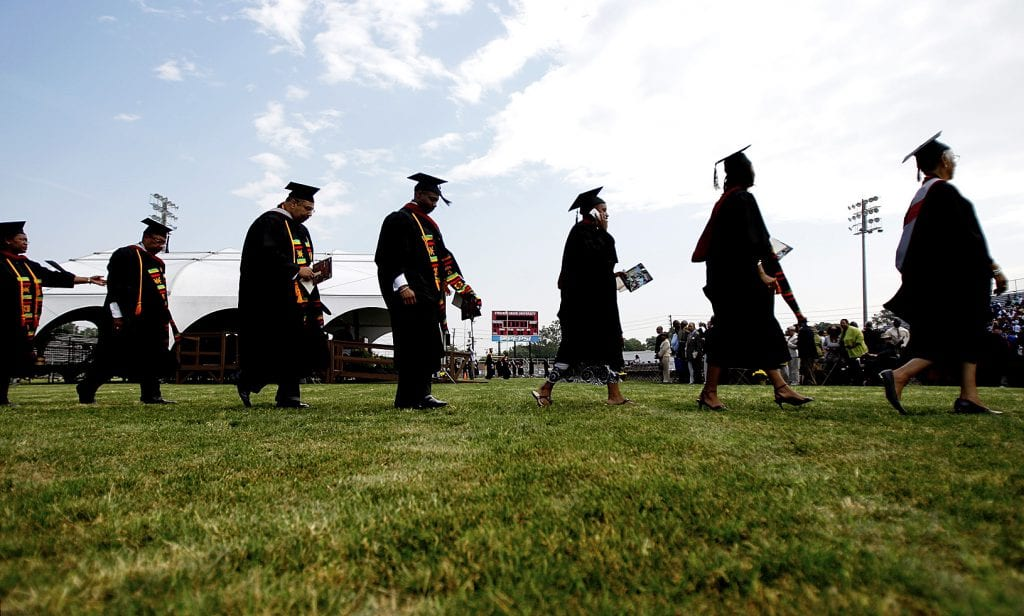 Group shot of Virginia Union University students walking to graduation ceremony wearing caps and gowns