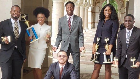 Group shot of Wiley College debate team members holding trophies