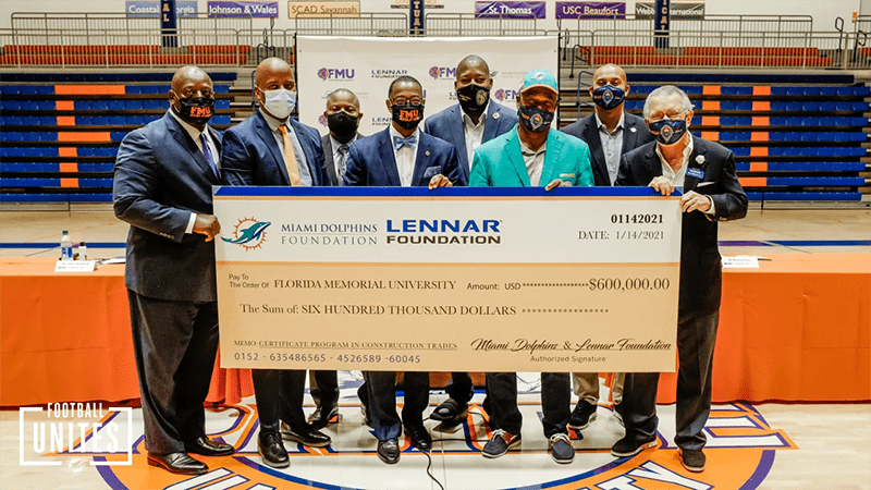 A group holds up a donation check for $600,000 from the Miami Dolphins