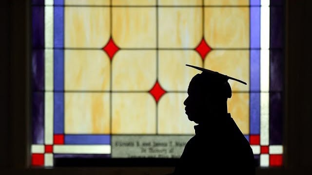 Student at Paine College in cap and gown in silhouette in front of stained glass window