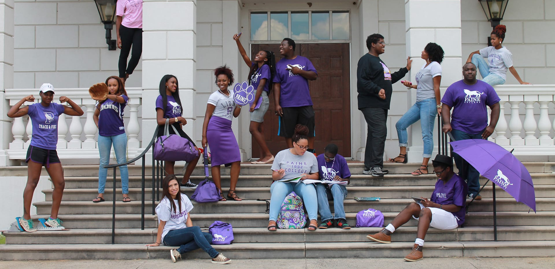 Posed photo of a group of students on the steps of a campus building