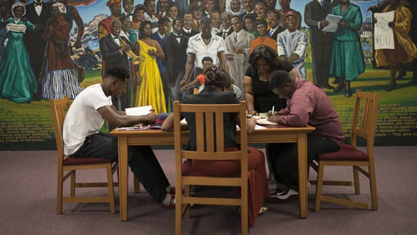 A group of students studying at a table in front of a mural
