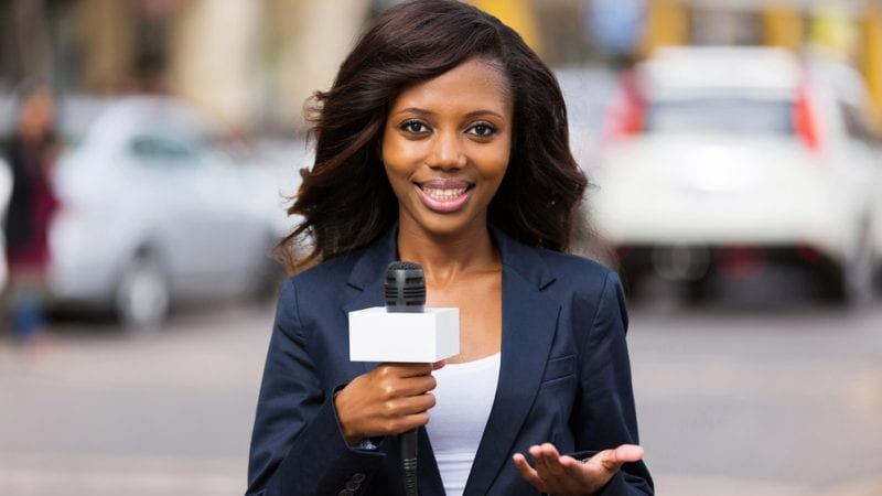 Female college student television reporter with microphone standing outside