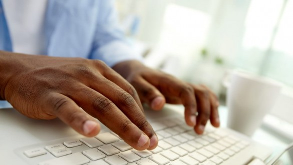 student hands typing on a keyboard
