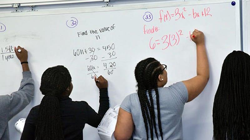 spellman students at whiteboard doing math